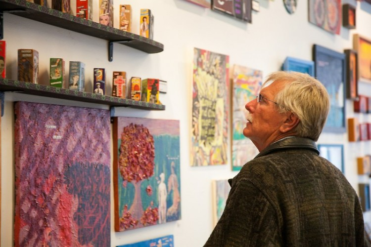 An Art.Downtown. attendee looks at the works displayed at Heartside Gallery.
