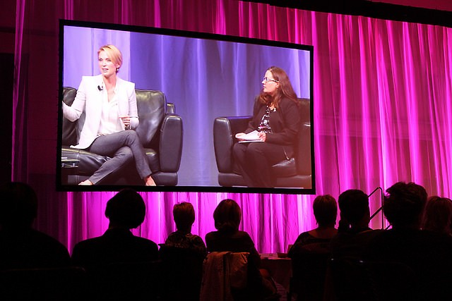 One of two large screens showing Amy Robach and Janelle Logan, Spectrum Health director of community engagement, on stage.