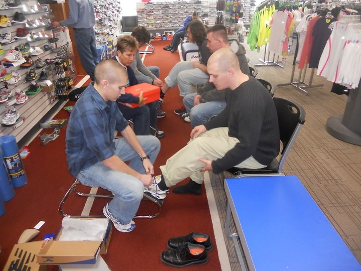 Sponsored runners from Guiding Light in the Fifth-Third River Bank 10K get fitted for shoes.