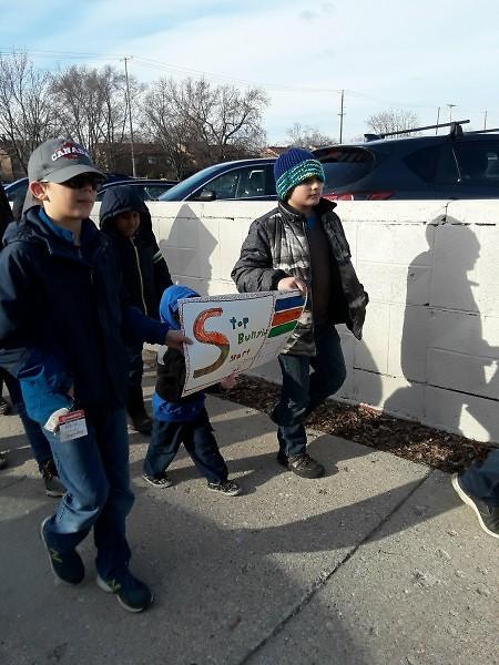 Nigel Doyle and Loki Ewigleben walk with their sign