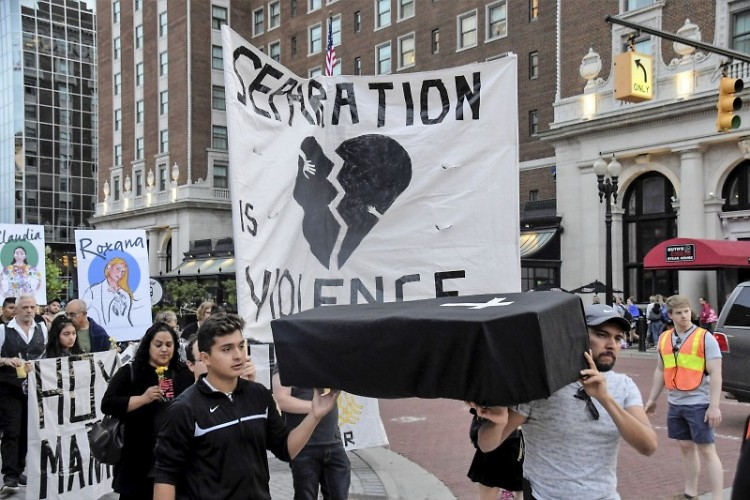 Marchers carry a symbolic coffin, mouring those who've been killed by ICE agents.