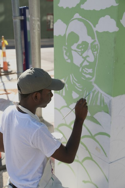 Chris Harris, 16, works on a mural of Ghandi at Fulton and LaGrave
