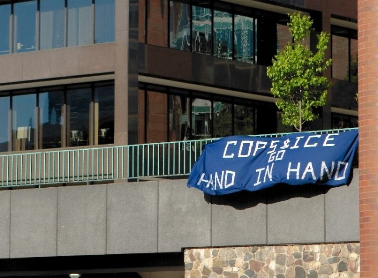 "A banner saying ""Cops and ICE Go Hand in Hand"" hangs off the Calder Plaza right before Tuesday's City Commission Meeting."