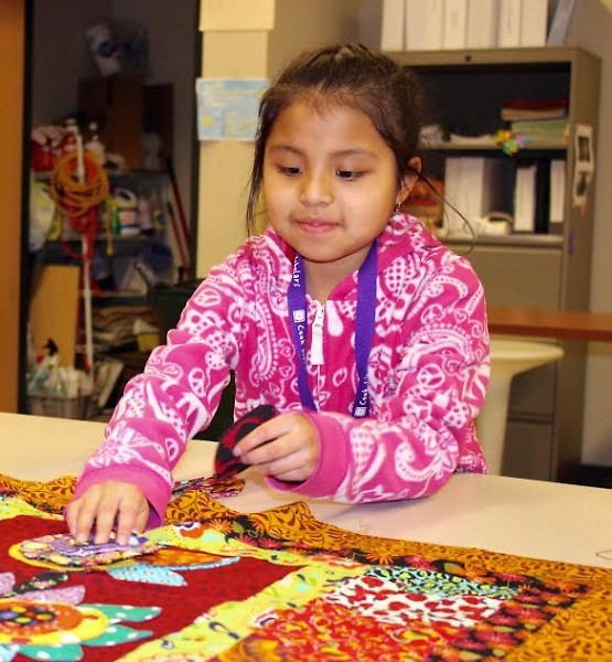 A student helping to make a quilt that was auctioned off at Día del Sol 2016