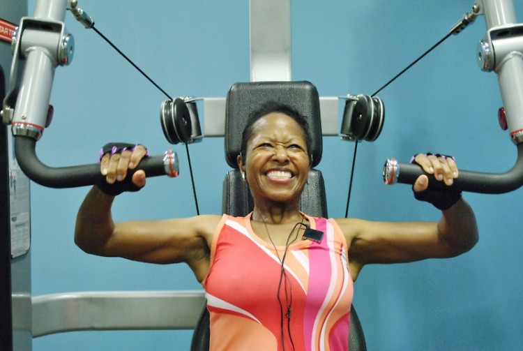 Leah Thomas listens to music as she uses the chest press machine in the Kroc Center. She lifts 40 pounds.