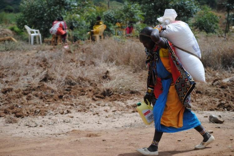 A woman carrying a Canadian Foodgrains Bank bag of grain