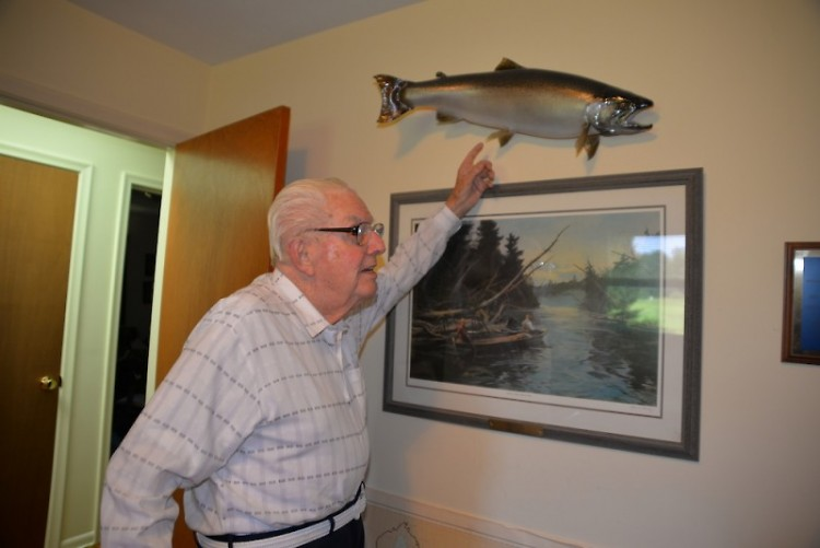 Acclaimed Michigan conservationist Howard Tanner shows off a mounted steelhead trout.