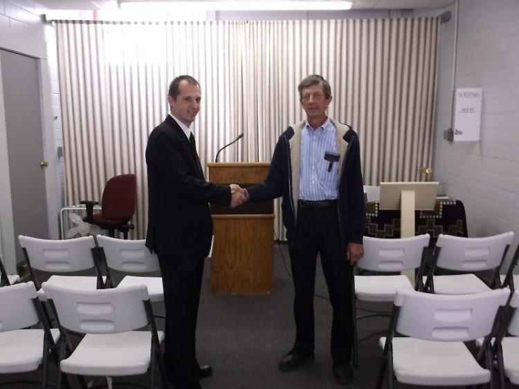 Presient of H.H.O.M. shakes hands with speaker Rev. Marteen Kuivenhoven Pastor of  Heritage Nethrlands Reformed Church.