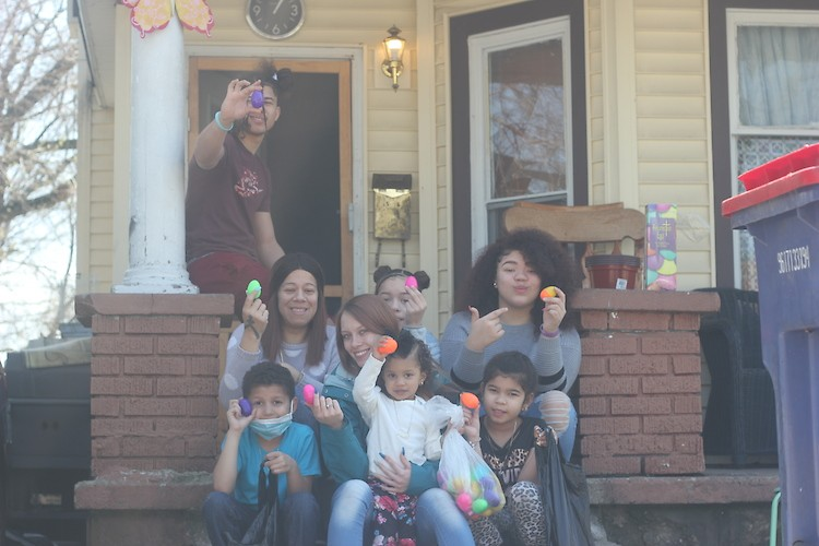 """A family shows off the eggs they received for the Community Kids """"home delivery"""" egg hunt."""