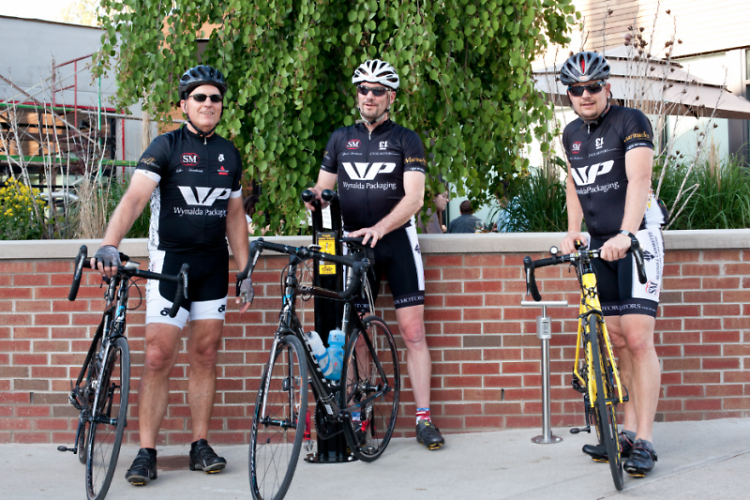 Team Speed Merchants Bike Shop of Rockford pose in front of the newly installed bicycle repair stand at Brewery Vivant