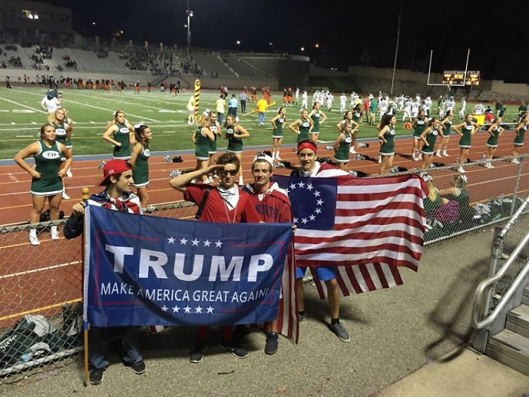 Students from Forest Hills Central displaying a Trump campaign flag and a Betsy Ross flag at a football game at Houseman Field.