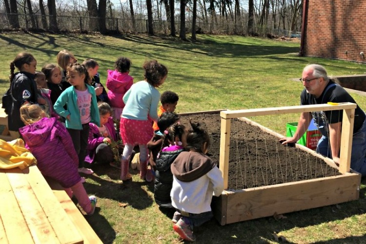 Preschoolers work with Jeff Smith from Gardens for Grand Rapids to build their garden.