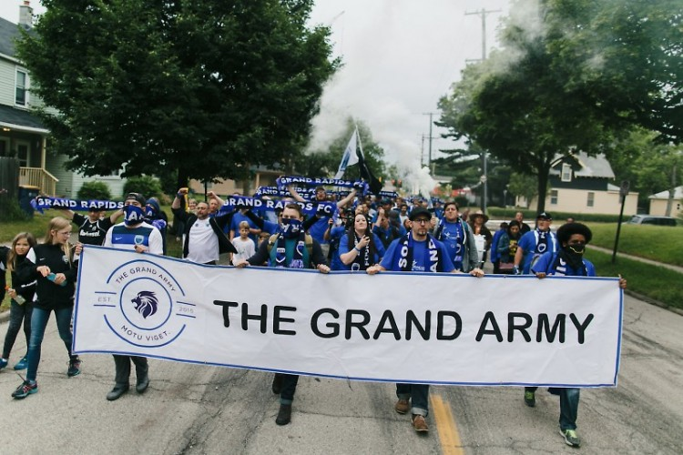 Grand Army members march from Bob's Sports Bar to Houseman Field prior to a Grand Rapids Football Club match last season.