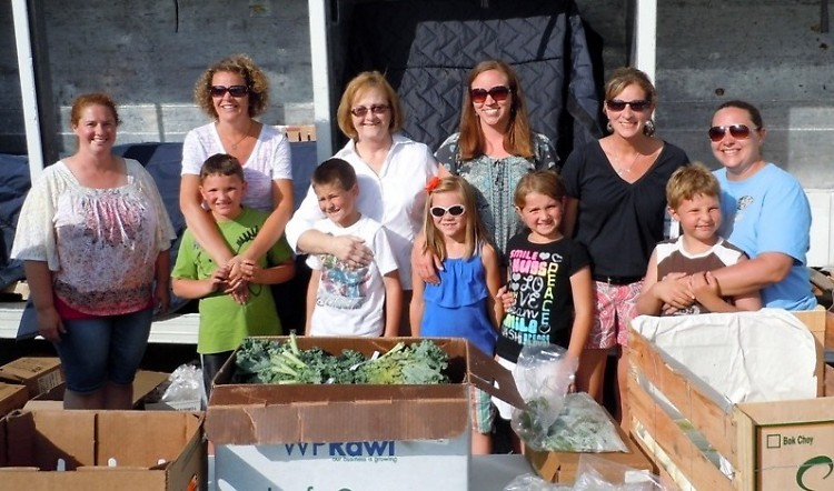 Nine-year-old Owen Ronning, center, raised money to bring a Mobile Food Pantry to Hudsonville last summer.