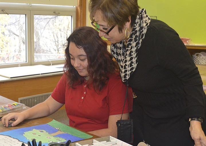 Southwest Community Campus Principal Carmen Fernandez talks to eighth-grader Angelica Morazan about her artwork