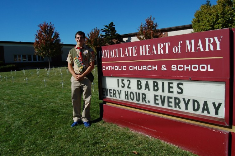 Tom Haley at Immaculate Heart of Mary Catholic Church and School, crosses in background