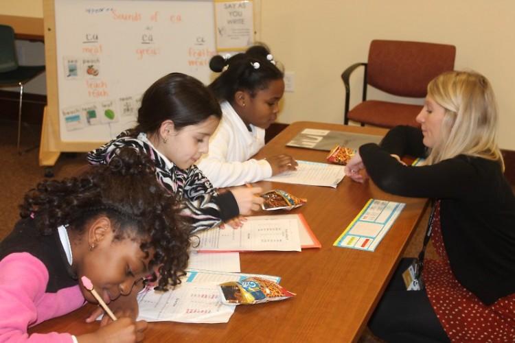Teacher Megan Brickner helps students with their homework