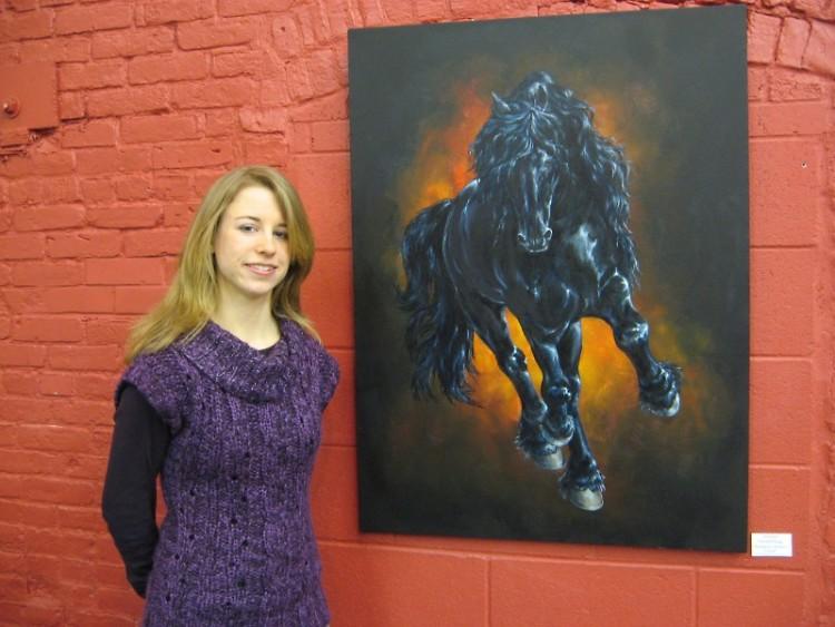 """Jennifer VanderPloeg beside her painting, """"Kampioen: Mintse's Portrait."""""""