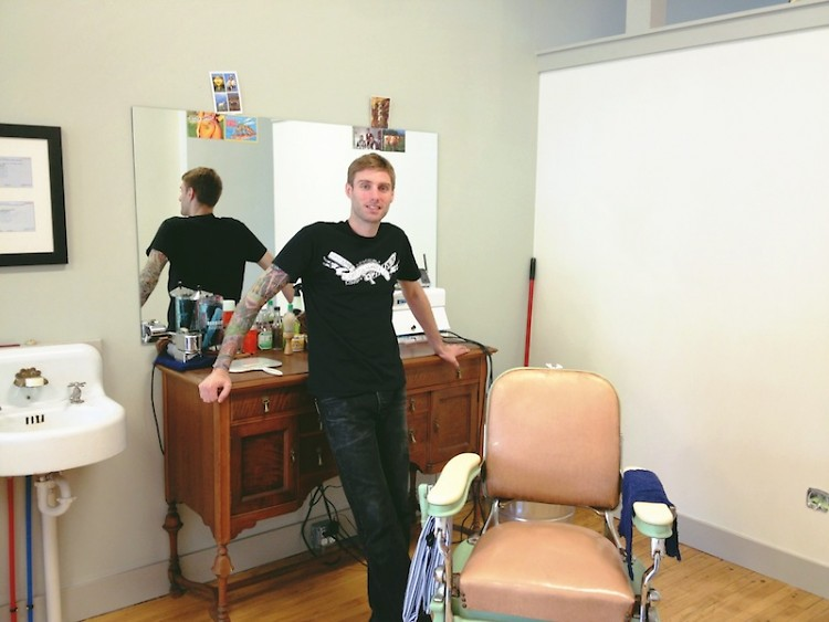 Andrew Theile, owner and operator of Foremost Barbershop, stands beside the barber chair