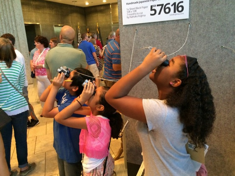 Young reporters look through binoculars to get a closer look at the detailed paper animal installation