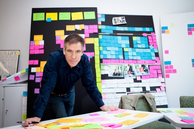 Starner in front of just a small collection of his visual boards.