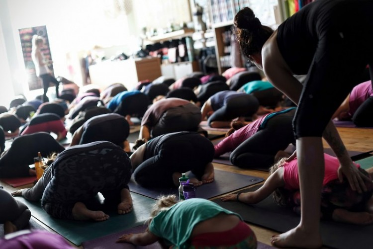 Mali Jane assists students in child's pose.