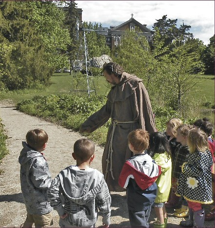 Sculptor Mic Carlson, dressed as St. Francis leads the children toward the Meditation and Sculpture Garden.