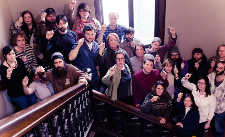 Community Media Center staff raise their pens to freedom of expression, speech and the press