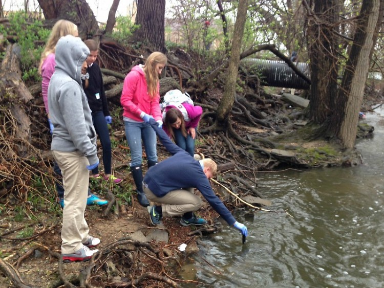 Middle school students collecting data from Plaster Creek