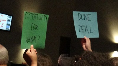 """Done Deal"" and ""Opportunity for Whom?"" Audience members hold up signs at the first AmplifyGR town hall in 2017."