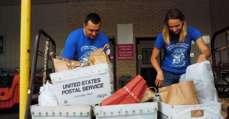 Feeding America West Michigan staff members Ryan VanMaldegen and Katie Auwers unpack Stamp Out Hunger donations, May 2015.