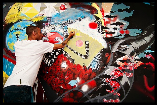 Artist from the Screwed Arts Collective installing mural at UICA.