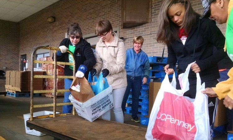 Staff and volunteers from Feeding America West Michigan unload food at the Kentwood Post Office branch.
