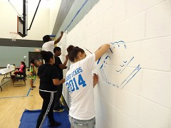 "Club members helping paint mural depicting their ""great futures."""