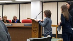 Two children giving speeches at the City Commission meeting in support of banning the use of wild animals for entertainment.
