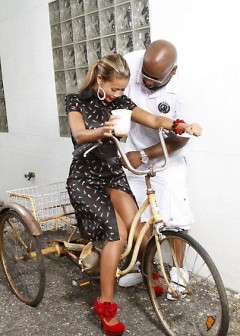 Celebrity stylist Kev Couture makes clothing adjustments to a model during a photo shoot.