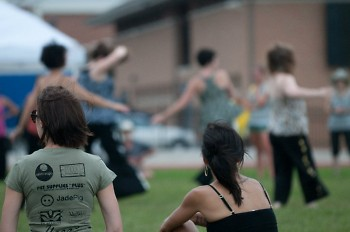 Festival founder Michele Fife (right) looks on as festival-goers try out yoga