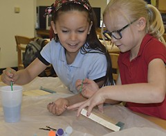 Elena Borjas-Garfio, left, and Morgan Williams paint miniature African hand pianos as part of the afternoon LOOP program