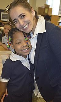 Harrison Park second-grader La'Rae Murray gets a warm hug from LOOP program supervisor Irma Alicia Lopez