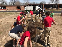 Students at All Saints Academy get a lesson in digging beds