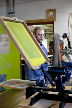 Anthony Reed at a four color silk screen press