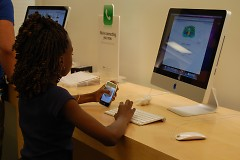 Club member enjoys playing at the Apple Store at Woodland Mall.