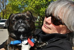 Frances Gentile snuggles with Phineas, one of the dogs she is hired to walk.