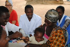 Baby and mother in Atekyedo receiving their first health screening by the Winneba Health Services Department Staff.
