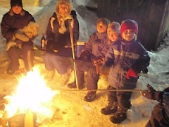 children warm up at the campfire in Dufferin Park in the city of Toronto