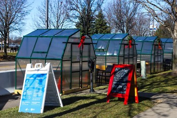 Greenhouse dining spaces outside Field & Fire Café on Monroe Ave. NW.