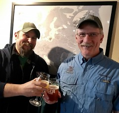 Jeff Knoblock (L) and Gary Evans, owner and head brewer, respectively, of Trail Point Brewing, toast with a glass of their beer.