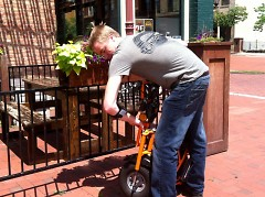 Chad Becker, owner of Your Chauffeur, folds bike for easy transporting