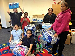 Local families and their students collect water at Harrison Park for Flint