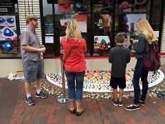 Zenz tells visitors the story behind his art outside the Grand Rapids Children's Museum.